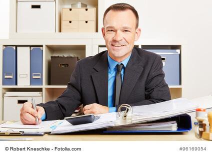 Steuerberater sitzt im Büro am Schreibtisch mit Akten und Taschenrechner