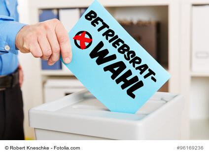 Hand mit Stimmzettel an Wahlurne für eine Betriebsratswahl